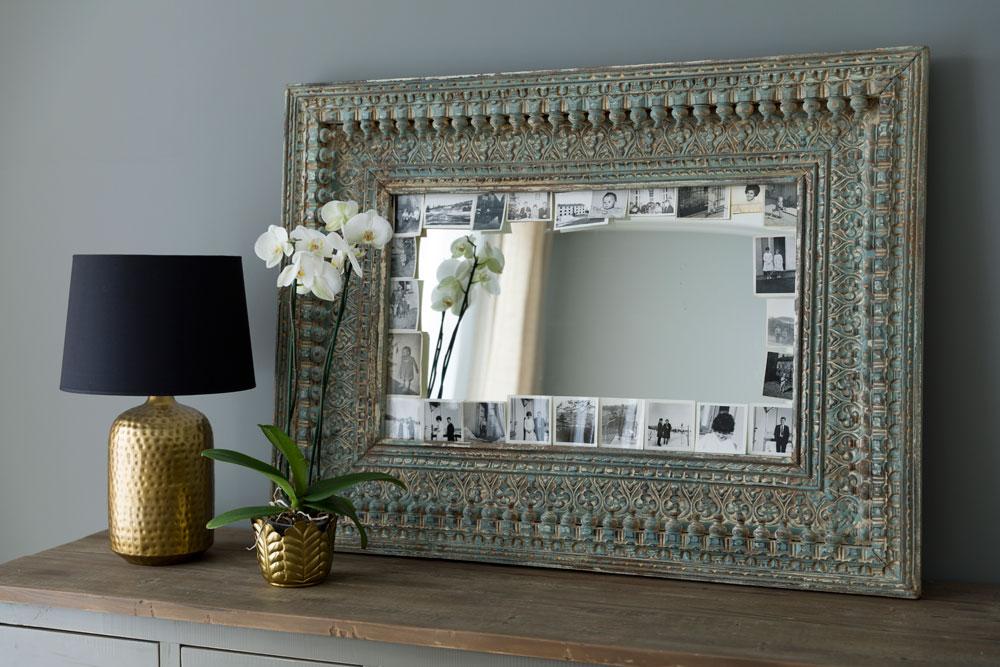 Speil med gamle sorthvitt fotografier stukket inn i bilderammen.