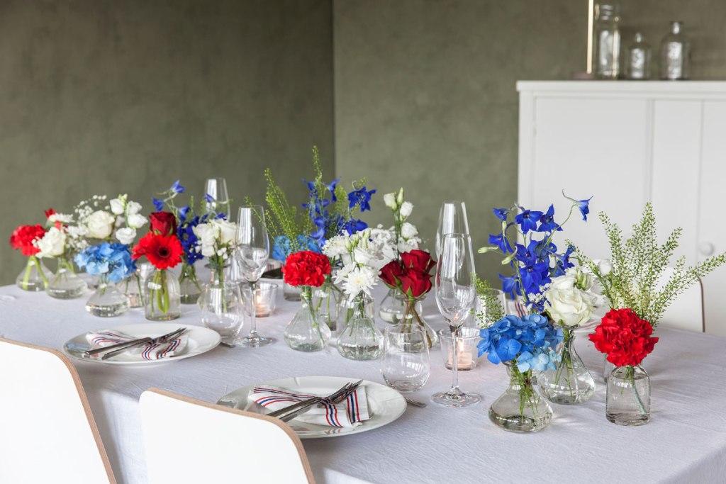 17. mai-bord og minivaser fylt med rødt, hvitt og blått