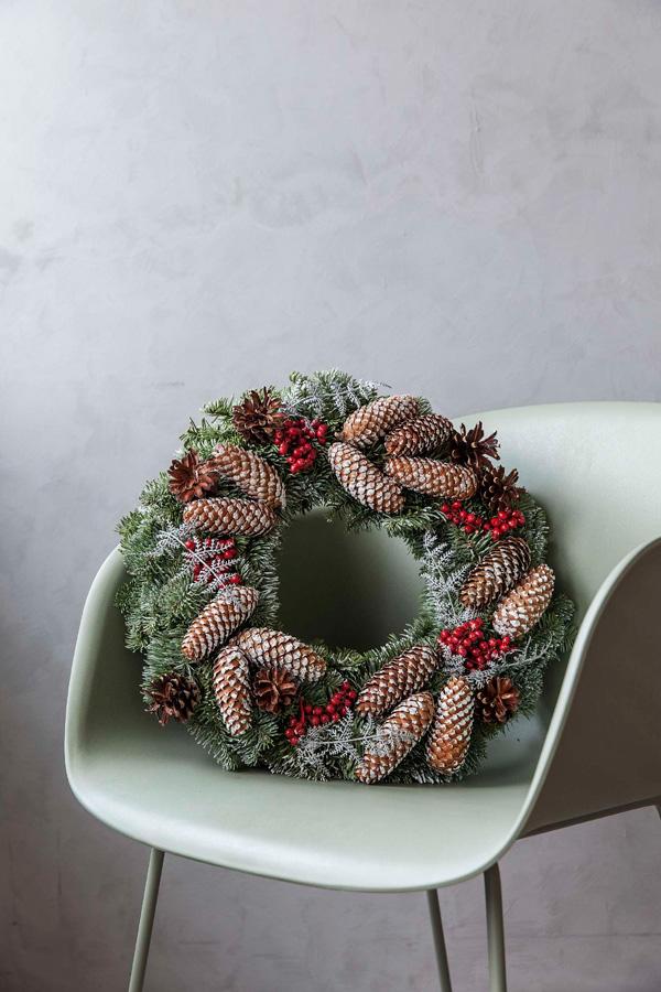 Julekrans med kongler og røde bær.