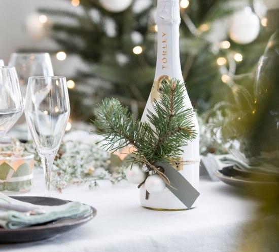 Vinflaske pyntet med julepynt til vertinnegave