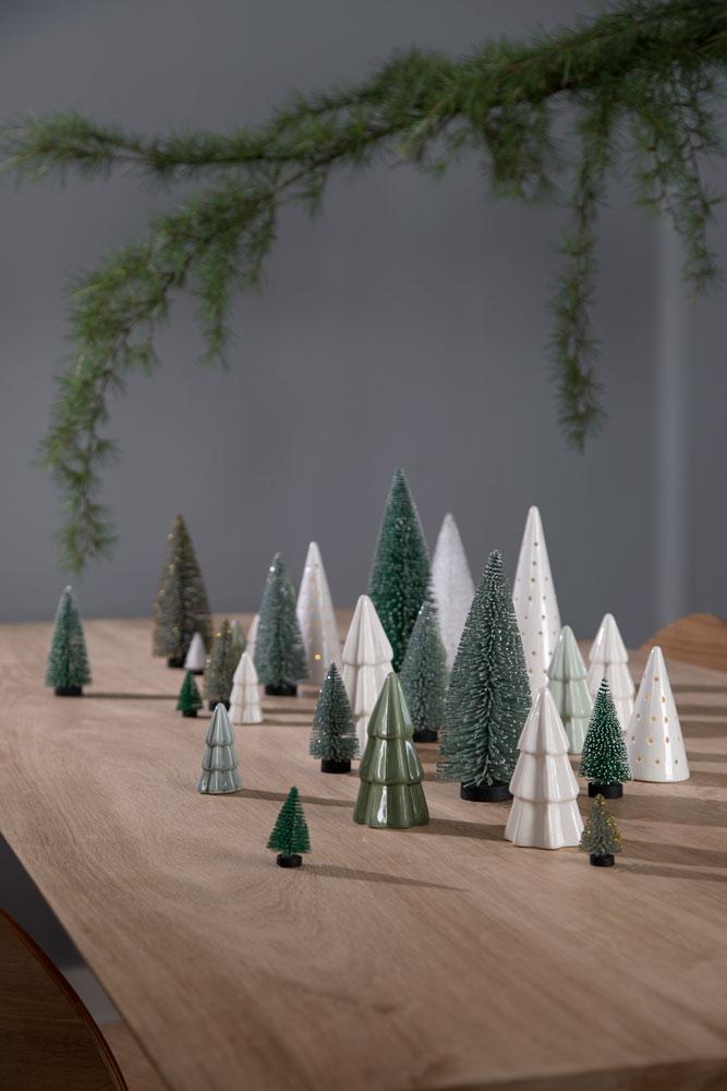 Bord med kunstige minijuletrær og juletrær i keramikk.