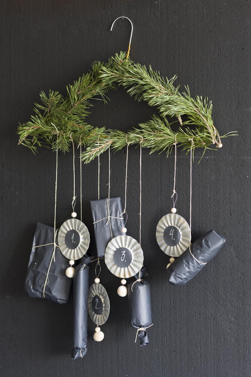 Adventskalender lagd av kleshenger med furukvister og julepynt av sandkakeformer.