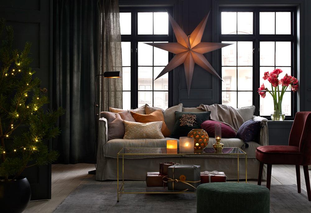 Julepyntet stue med adventsstjerne og levende lys.