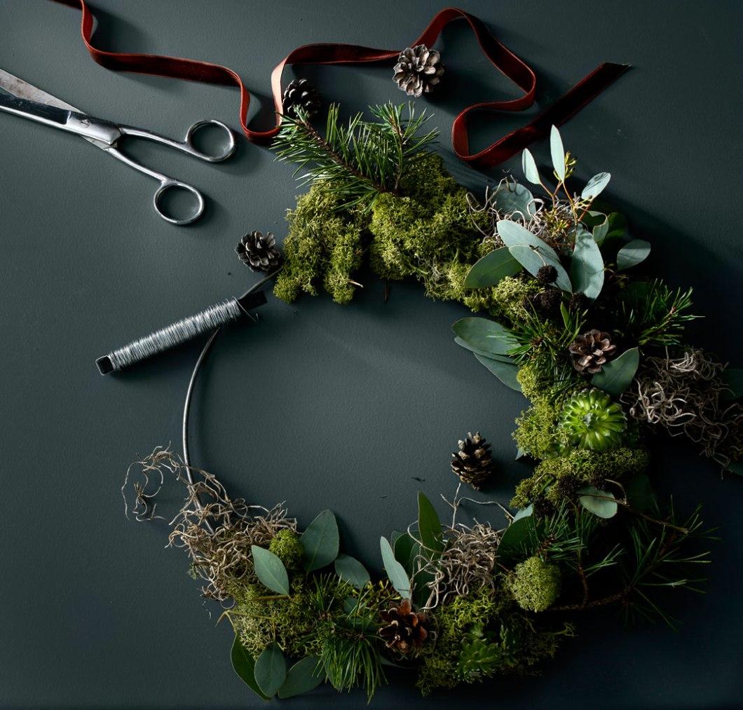 Krans av mose, eukalyptus, vintergrønt og kongler
