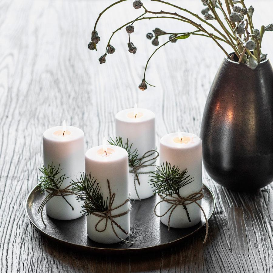 Enkel adventspynt: Fire hvite kubbelys på et fat.