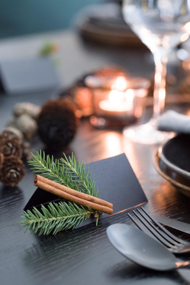 Sort bordkort med pynt av kanel og granbar.