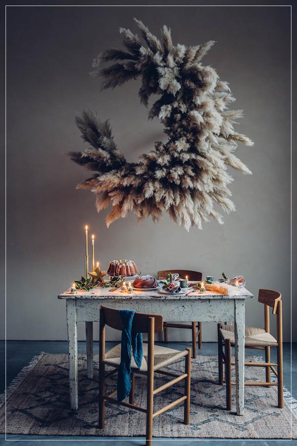 Rustikt bord med overdådig blomsterdekorasjon med pampasgress hengende ned fra taket.
