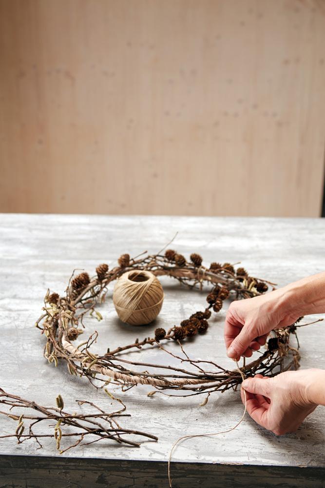 Adventskrans av solid ståltråd, løst dekket med grener fra hassel og lerk.