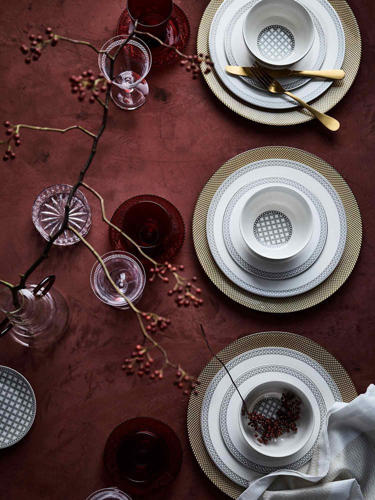 Borddekking i vinrødt med servise i hvitt og gull.