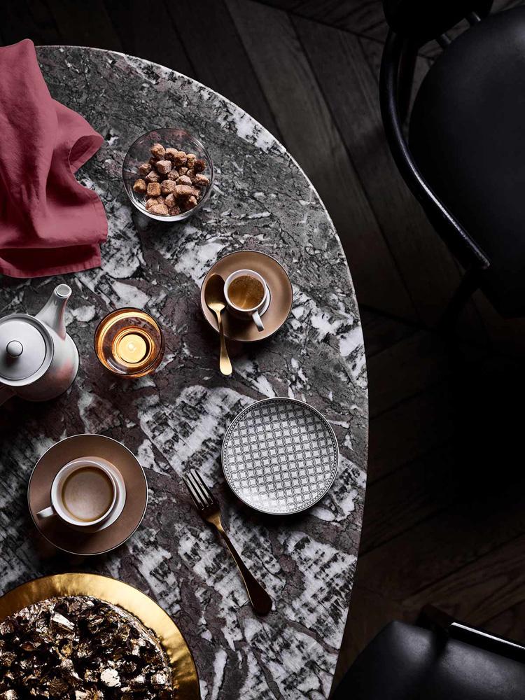 Borddekking av kaffebord i hvitt, brunt, sort og gull - og med tekstiler i vinrødt.