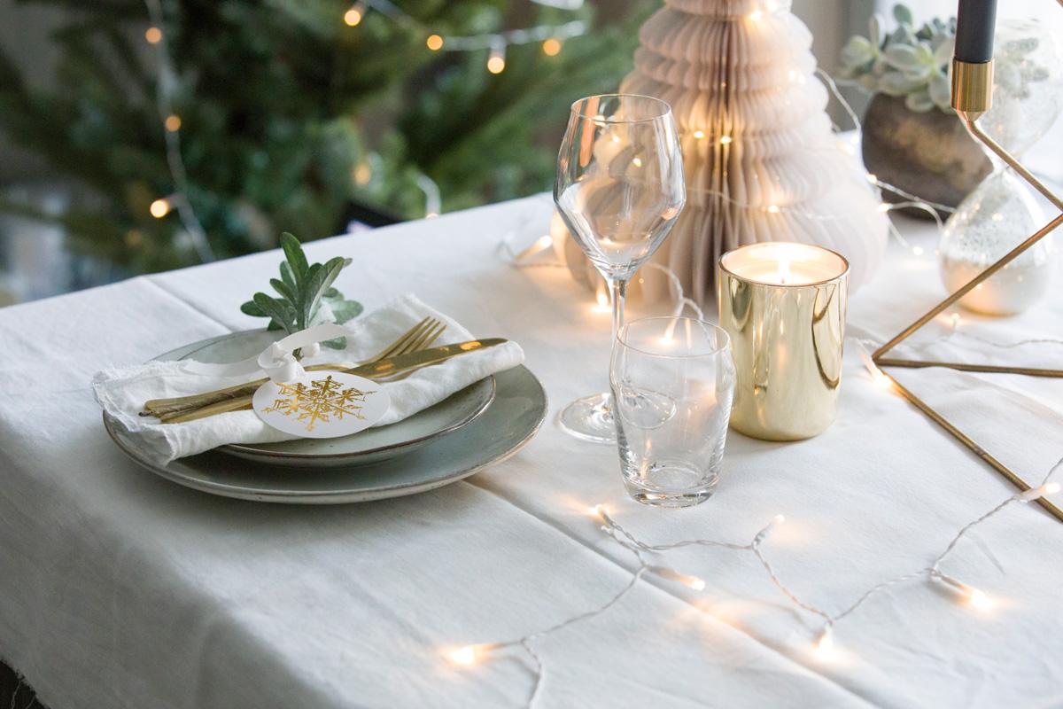 Dekket julebord i hvitt og gull.