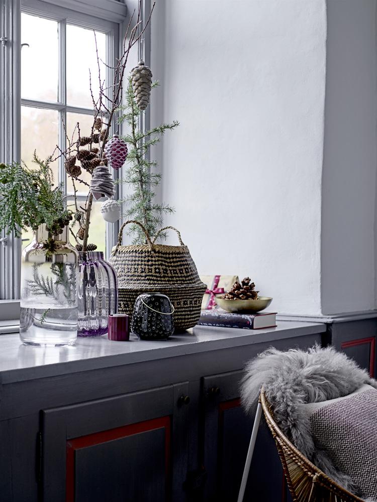 Vinduskarm dekorert med julepynt og naturmaterialer.