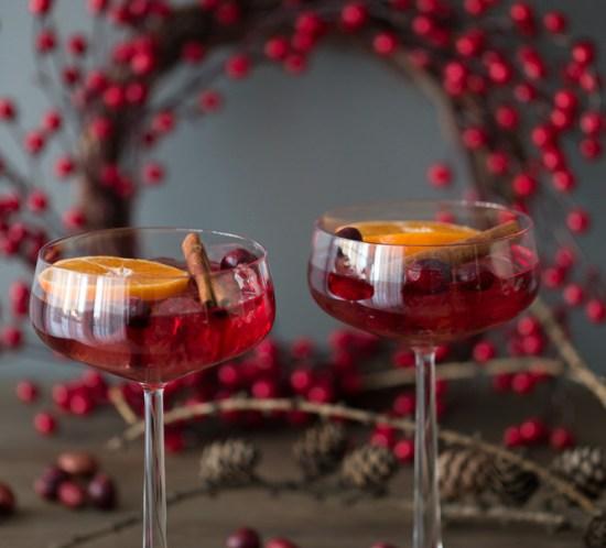 Rød velkomstdrink med tranebær- og granateplejuice. Pyntet med klementinskive, kanelstang og tranebær.