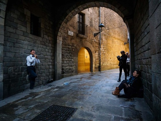 A street musician sings while a woman feels in extasis, under an arch in the Gothic Quartier, during sunset