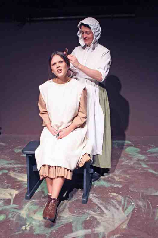 Photograph of Mrs Beamish, played by Marie Cooper, braiding her daughter Martha's hair in Lark Rise, Sewell Barn Theatre in Norwich