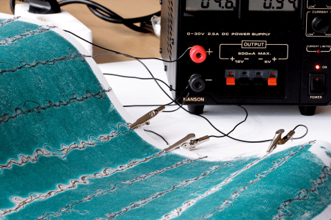 Script is a thermochromicly (heat sensitive) printed nonwoven with embroidered circuits. The textile is connected to a power pack.