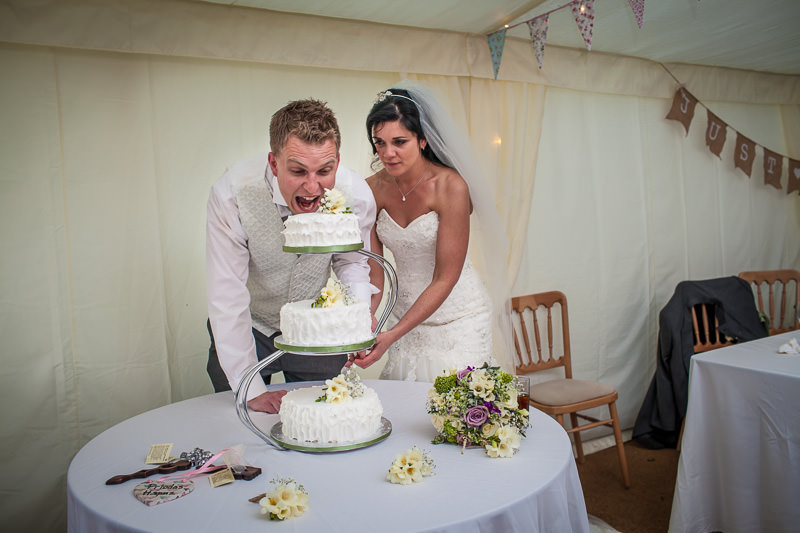Groom going for an early bite of the wedding cake
