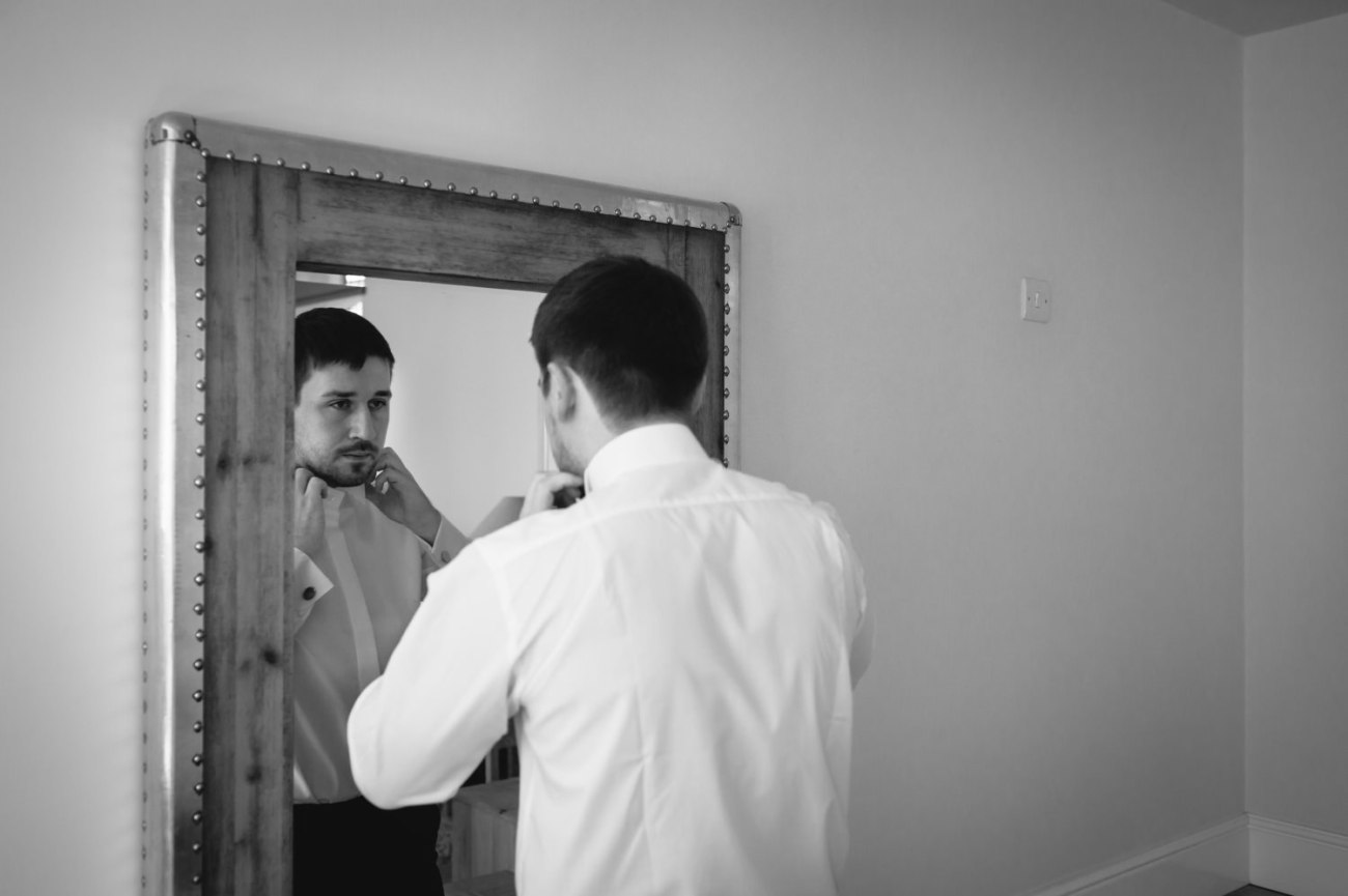 Black and white wedding photography of groom getting ready at Cheshire venue Colshaw Hall
