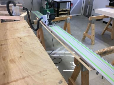 Using the tracksaw to rip a straight edge of some of the lumber.