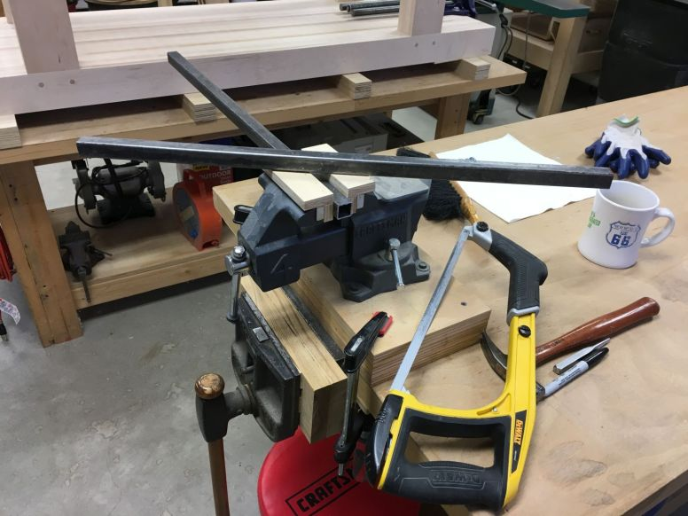 Cutting two 24 inch lengths of square steel tubing to connect retractable caster levers