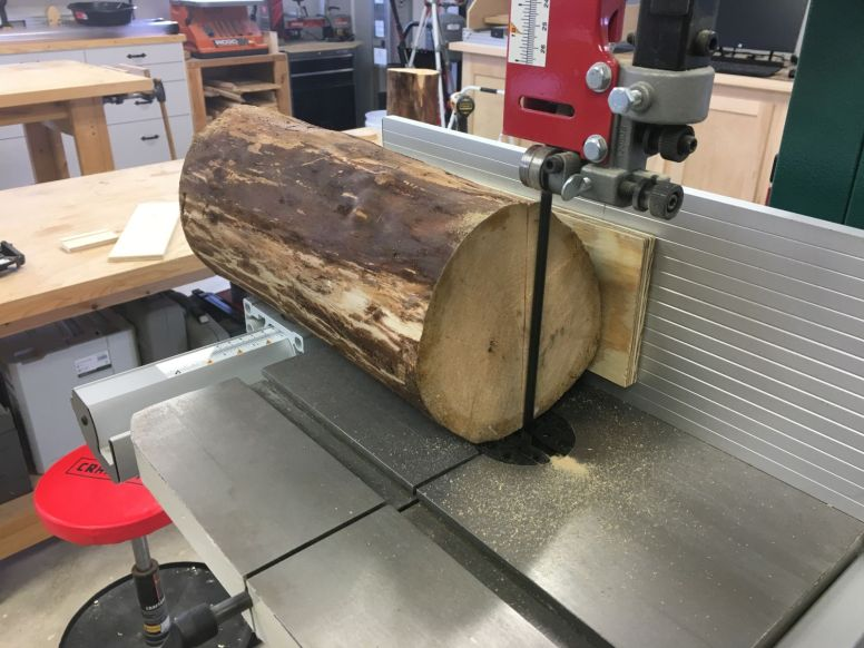 Sawing debarked cherry log sections on the bandsaw with a board screwed to the side as a guide