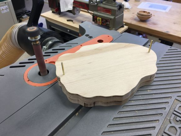 Sanding the edges of back and front pieces pinned together, on the oscillating drum sander