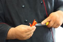 A vietnamese chef slicing chili