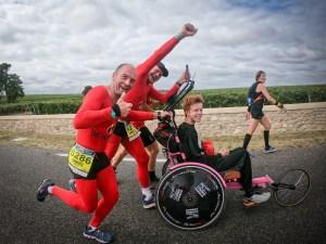 Coureurs poussant un handicapé au marathon du médoc