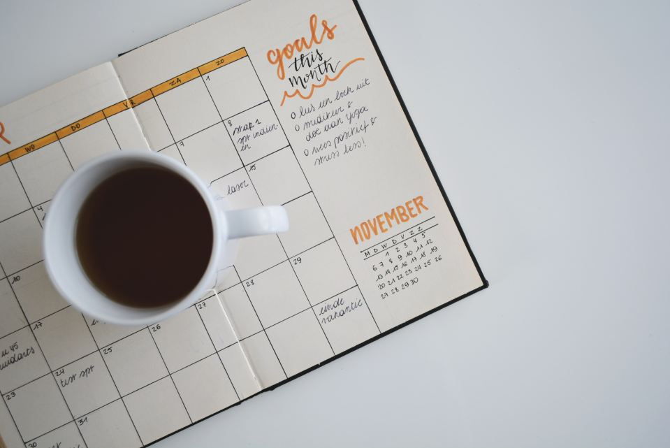 A mug full of coffee on an open planner