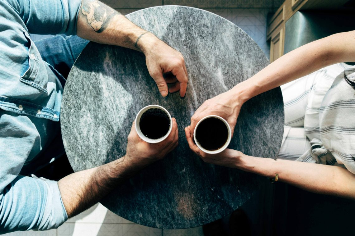 Top down shot of two people sitting across from each other a table having coffee with just their arms and cups in view