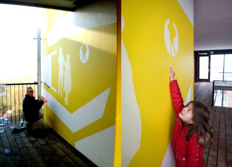 Een bewoner aan het werk en een van de jongste deelnemers trots op haar eigen silhouette.