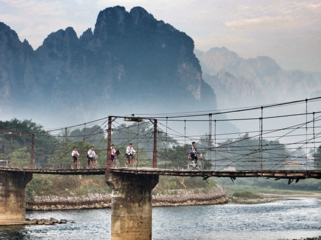 Watching kids bike to school from our breakfast table in Vang Vieng. We later spent three wonderful hours floating leisurely down this river on tractor inner tubes.