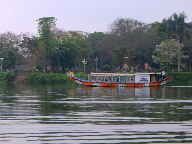 A tourist boat, identical to ours, heading south down the Perfume River to explore the emperors' tombs