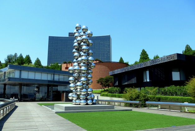 The three buildings that make up Leeum, Samsung Museum of Art, with the statue Tall Tree and the Eye in the foreground and the Grand Hyatt hotel looming in back