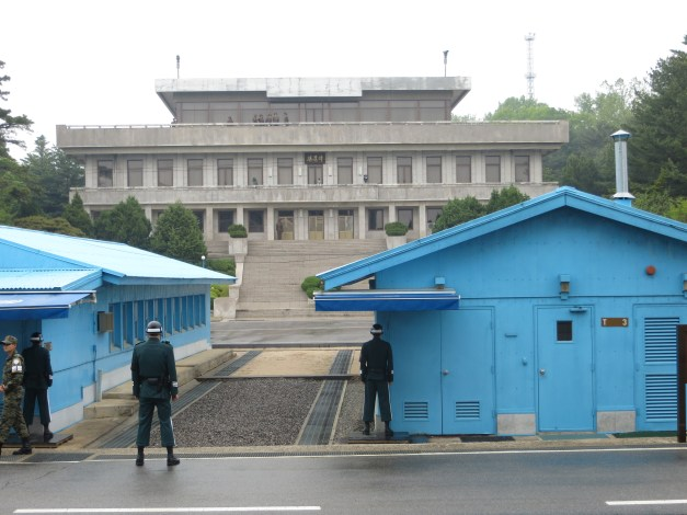 The Joint Security Area at the border between North & South Korea. These are South Korean soldiers, with the sentry standing half exposed and half hidden, to minimize the amount of target he exposes to the North. The building in the background is in North Korea, with high-ranking military officials on the upper balcony watching us (or, more likely, watching the military people all around us).