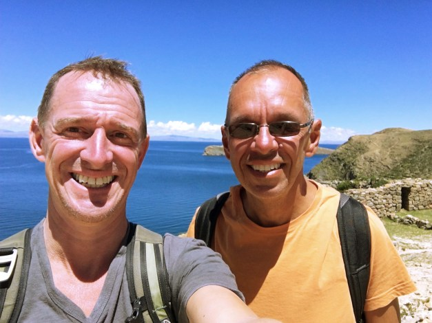 Happy traveloholics hiking across Isla del Sol in Lake Titicaca