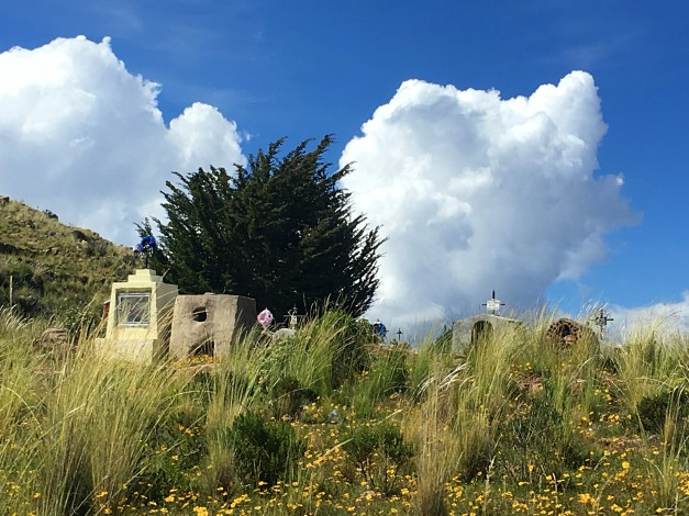 A cemetery peeks out from the roadside, backed by those stunning Andean clouds