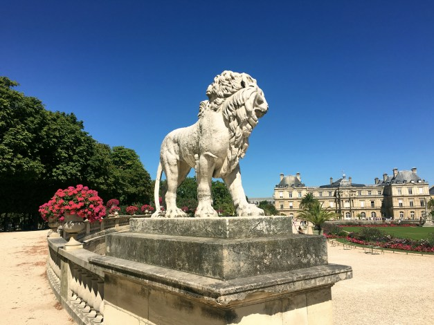 A lion along with beautiful flowers in the Luxembourg Garden