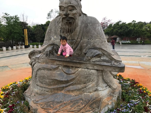 Cute girl posing on a statue of Confucius