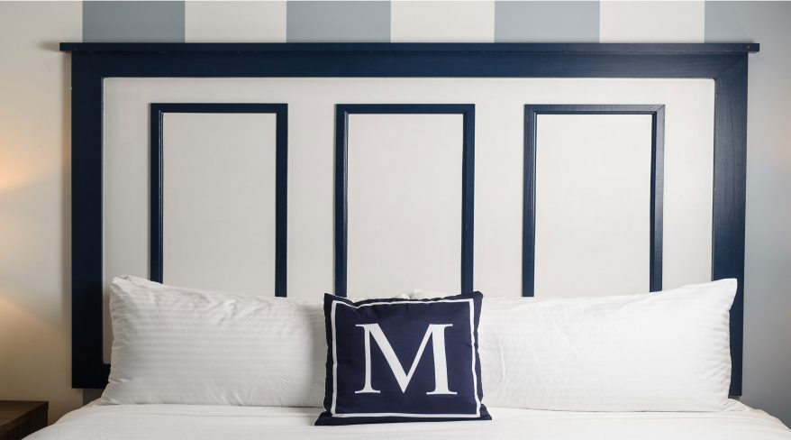 Queen Bed with White Sheets and Blue Pillow with an M on it.