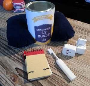 La box Découvrir le monde contient 4 produits : un kit d'adaptateurs de prises, un oreiller de cou gonflable, une brosse a dent de voyage et un carnet.
