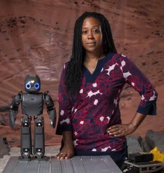 A headshot of roboticist Ayanna Howard standing next to a robot.