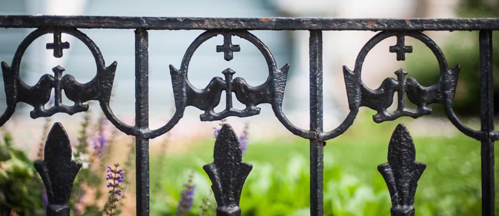 Rod iron fence with two birds kissing cut outs with yard in background