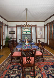 Dining room with glass table and set up for breakfast, striped wallpaper