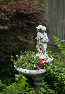 Water fountain filled with white and red plants, has a figure of Boy and Girl