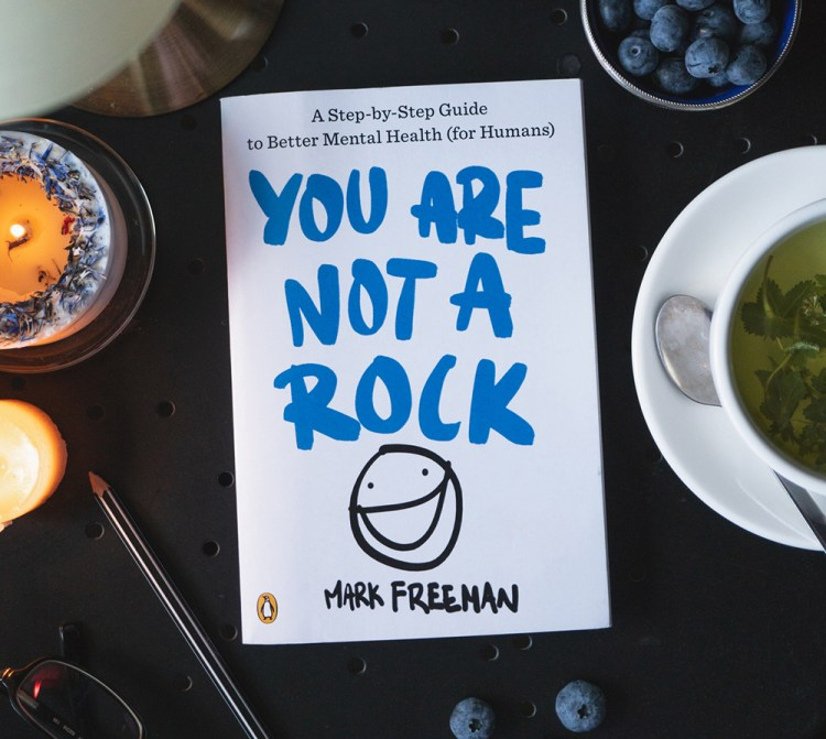 Photo of book, YOU ARE NOT A ROCK, on a table that has candles, green tea, blue berries, and a pen on it.