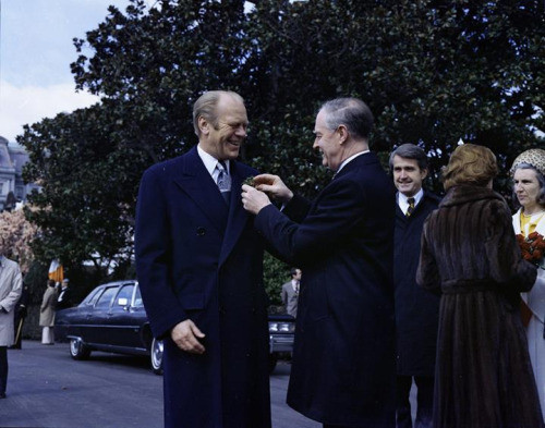 Liam Cosgrave pins a shamrock to the lapel of Gerald Ford.