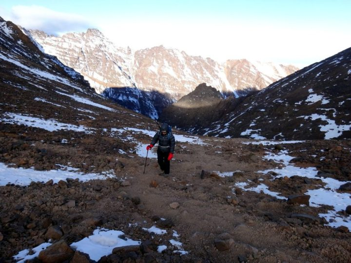 Ascending wind-blasted slopes on the way up to the col between Toubkal and Toubkal West