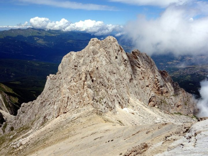Corno Piccolo extends from a shoulder of Corno Grande like a scaly arm of jagged rock pinnacles