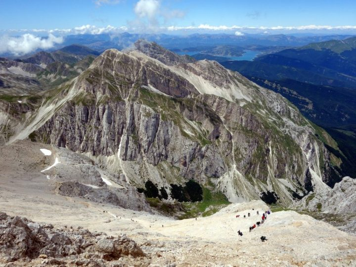 Hikers on Via Normale, Corno Grande, with Pizzo d'Intermesoli, Monte Corvo and Lago di Campotosto behind
